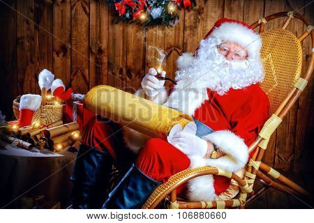 Santa Claus sitting at his wooden house in a comfortable chair, smoking a pipe and reading a letter.