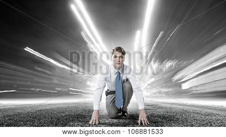 Young determined businessman in starting position ready to compete