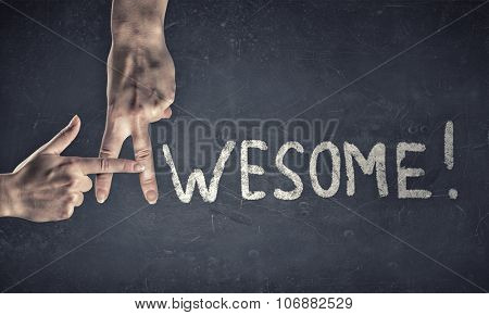 Awesome word written on wall and fingers instead letter A