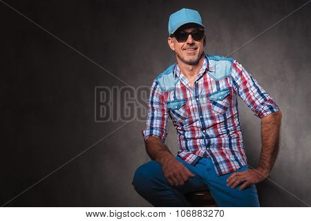 confident old casual man with baseball hat and sunglassed sitting and looks away from hte camera
