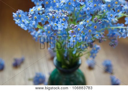 bouquet of forget me nots in green vase