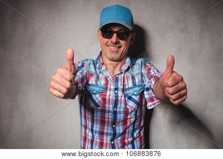 aged happy casual man making the ok thumbs up hand sign in studio