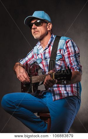 side view of a senior rock and roll man playing electric guitar , sitting on a chair and looking away from the camera