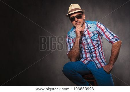 serious thoughtful senior casual man wearing summer hat and sunglasses looking at the camera while seated in studio