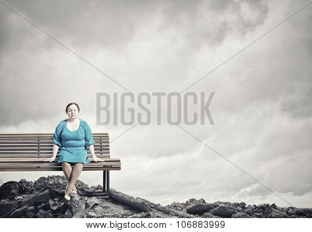 Middle aged stout woman in blue dress sitting on bench
