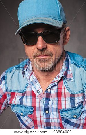 head and shoulders picture of a senior casual man wearing baseball hat and sunglasses, looking at the camera