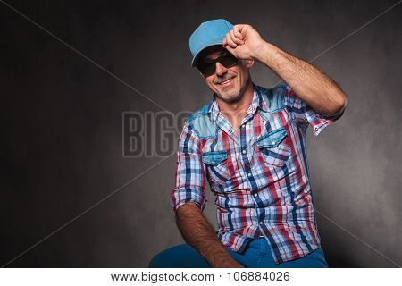 happy senior casual man holding his hat in a greeting pose, saying hello, in studio