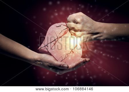Close up of human hand breaking stone heart