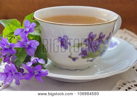 china tea cup with pattern of violets and bouquet of violets on the white tablecloth