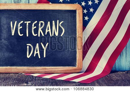 the text veterans day written in a chalkboard and a flag of the United States, on a rustic wooden background