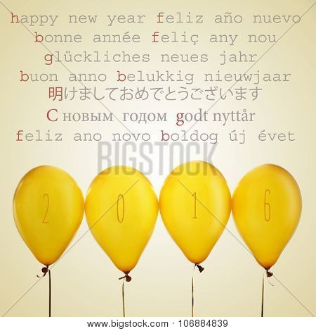 four golden balloons with the number 2016 and the text happy new year written in different languages, such as spanish, french, catalan, german, russian or japanese