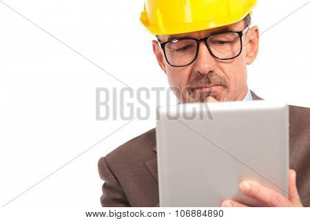 concerned senior construction engineer reading on his tablet computer on white background