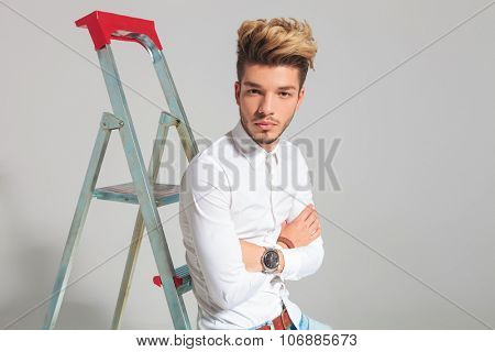 portrait of man leaning against a ladder with hands crossed while posing in studio background