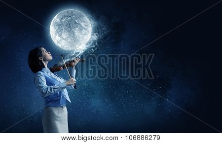 Young woman playing violin and full moon in sky