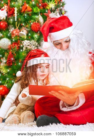 Portrait of little charming baby girl with Santa Claus reading magical Christmas story, enjoying wonderful festive fairy tale