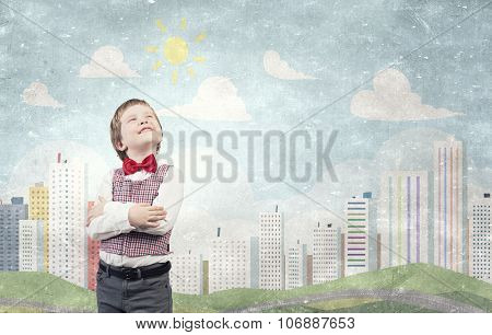 Portrait of little boy with hands folded on chest