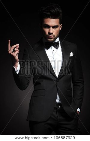 Picture of a young elegant business man snapping his fingers while looking at the camera.