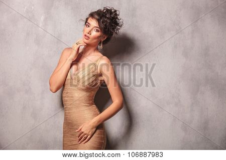 beautiful woman pose standing while touching her chin with her hand