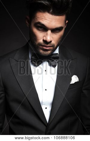 Portrait of a handsome elegant business man looking at the camera with, lifting one eyebrow.