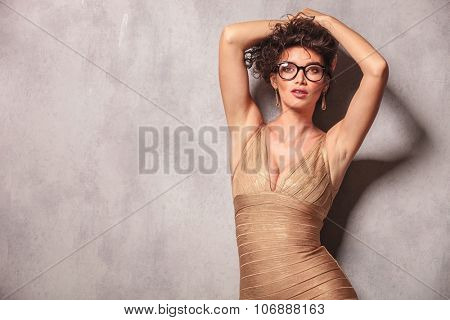 sexy woman pose looking at the camera while holding her hair up with both hands