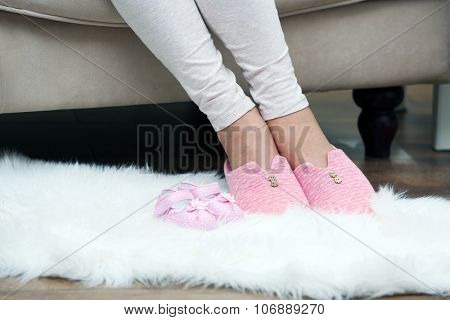 Woman's foots in slippers and baby's booties on soft white carpet in the room