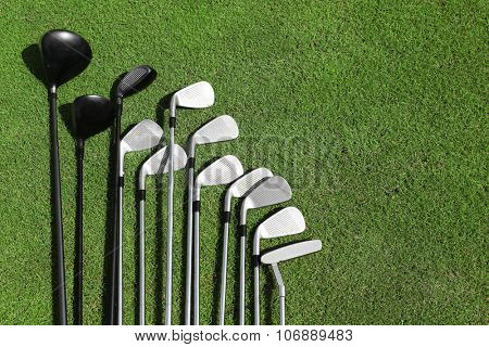 Different golf clubs in a row on a green grass