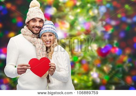 love, valentines day, couple, christmas and people concept - smiling man and woman in winter hats and scarf holding red paper heart shape over holidays lights background