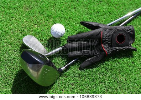 Golf clubs with ball and black glove on a green grass, close up