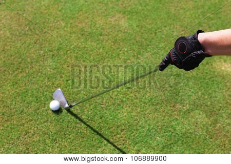 Hand in black glove with golf club and ball on green grass background