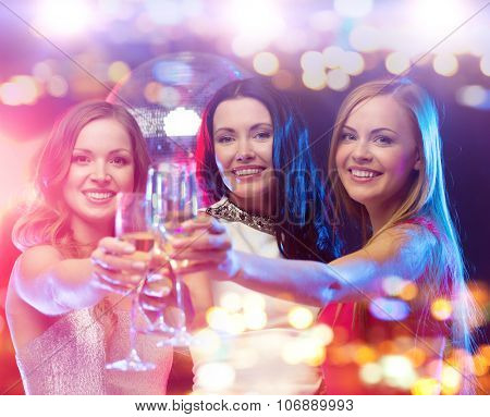 holidays, nightlife, bachelorette party and people concept - smiling women with champagne glasses at night club