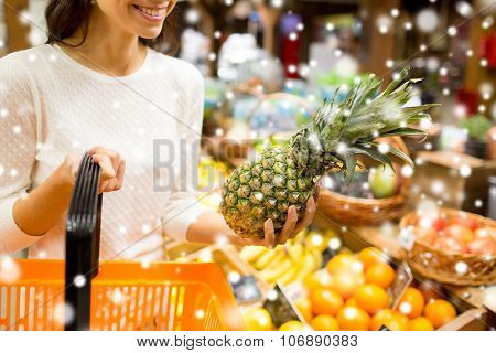 sale, shopping, consumerism and people concept - close up of young woman with food basket and pineapple in grocery market over snow effect