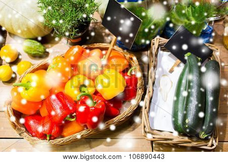 sale, shopping and eco food concept - ripe vegetables in baskets with nameplates at grocery market over snow effect