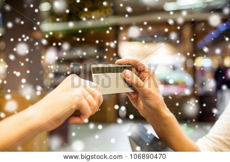 sale, shopping, payment, consumerism and people concept - close up of hands giving credit card at checkout in market or mall over snow effect