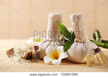 Natural spa set with massage balls, salt, aroma oil and frangipani flower with bamboo on wicker background