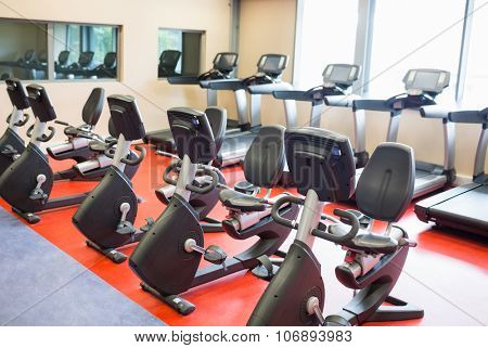 Row of treadmills and exercise bikes at the gym