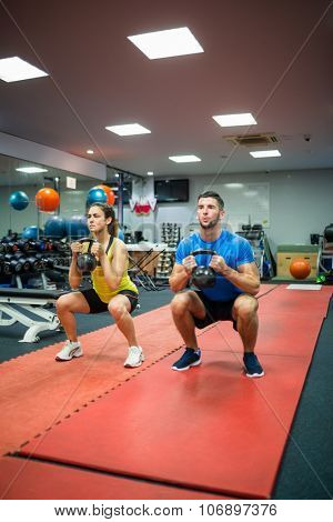 Couple crouching down while holding kettlebells at the gym