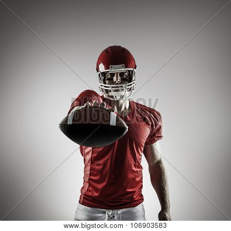 American football player showing ball against grey vignette