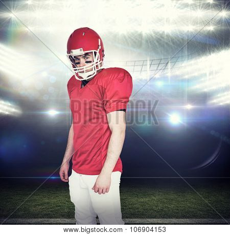 Serious american football player looking at camera against american football arena