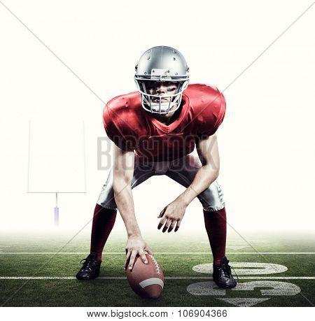 American football player holding helmet against american football posts