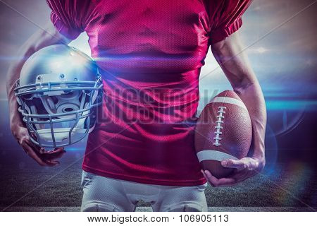 Midsection of American football player holding helmet and ball against american football arena
