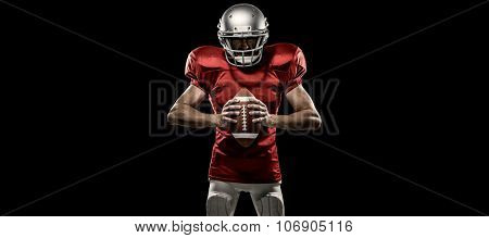 Furious American football player in red jersey and helmet holding ball against black