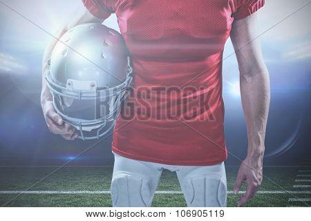 American football player holding helmet aside against american football arena