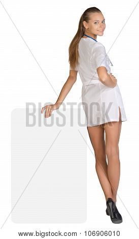Young woman doctor standing backward, leaning hand on an empty billboard