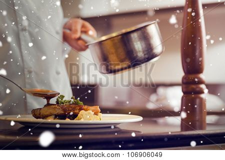 Snow against closeup mid section of a chef garnishing food