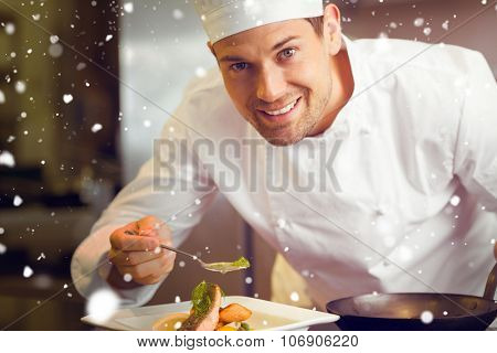 Snow against smiling male chef garnishing food in kitchen