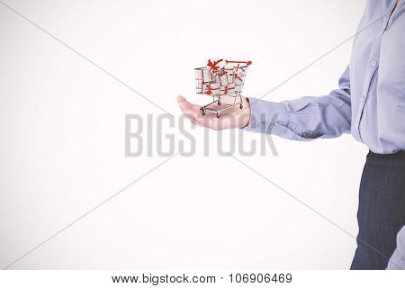 Businesswoman presenting with hand against trolley full of gifts