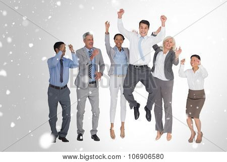 Business people cheering in office against snow