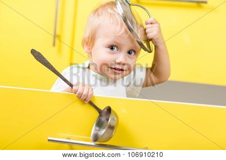 Kid sitting inside yellow opened kitchen box with laddle