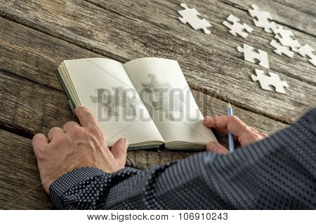 Man Sketching Two Matchng Puzzle Pieces In His Notepad