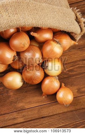 Scattered sac with fresh onions on wooden background